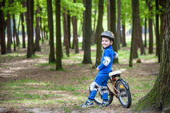 Happy kid boy of 4 years having fun in autumn or summer forest with a bicycle Royalty Free Stock Image