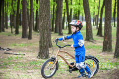 Happy kid boy of 4 years having fun in autumn or summer forest with a bicycle Royalty Free Stock Images