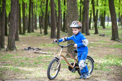 Happy kid boy of 4 years having fun in autumn or summer forest with a bicycle Stock Image