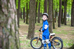 Happy kid boy of 4 years having fun in autumn or summer forest with a bicycle on beautiful fall spring day. Active child making sp Royalty Free Stock Photography