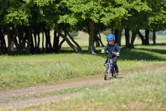 Happy kid boy of 5 years having fun in spring forest with a bicycle on beautiful fall day. Active child wearing bike helmet. stock image
