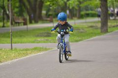 Happy kid boy of 5 years having fun in spring park with a bicycl. E on beautiful fall day. Active child wearing bike helmet Stock Photos