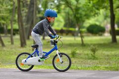 Happy kid boy of 5 years having fun in spring park with a bicycl. E on beautiful fall day. Active child wearing bike helmet Royalty Free Stock Photography