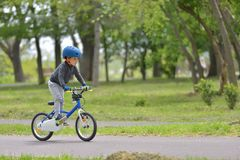 Happy kid boy of 5 years having fun in spring park with a bicycle. On beautiful fall day. Active child wearing bike helmet Royalty Free Stock Photo