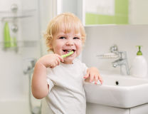 Happy kid brushing teeth in bathroom Stock Photo