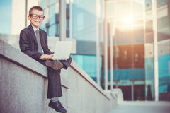 Happy kid businessman with laptop stock image