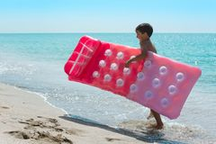 A happy kid carries a mattress along the surf line. royalty free stock images
