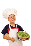 Happy kid with chef hat and a bowl of green peas Royalty Free Stock Photography