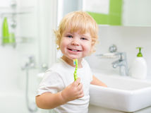 Happy kid or child  brushing teeth in bathroom Royalty Free Stock Photo