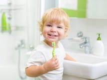 Happy kid or child  brushing teeth in bathroom