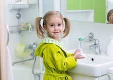 Happy kid or child brushing teeth in bathroom. Dental hygiene. stock image