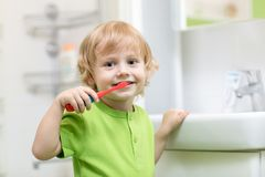 Happy kid or child brushing teeth in bathroom. Dental hygiene. Happy kid or child boy brushing teeth in bathroom. Dental hygiene Royalty Free Stock Images