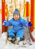 Happy kid on children playground in winter Royalty Free Stock Photography