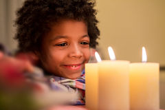 Happy kid beside Christmas candle. royalty free stock image