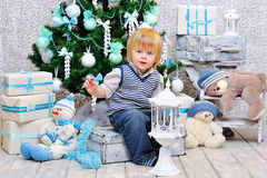 Happy kid by the Christmas tree Royalty Free Stock Images