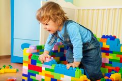 Happy kid claiming out of toy block. In his room Stock Photos