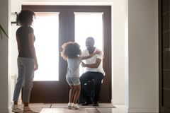 Happy kid daughter excited to meet african dad arriving home. Happy kid daughter excited to meet african american dad arriving coming home after business trip stock photo