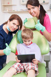 Happy kid at dentist playing with wireless tablet Royalty Free Stock Images