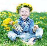 Happy kid with diadem and dandelions royalty free stock image