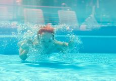 Happy kid dives underwater in the pool Royalty Free Stock Image