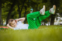 Happy kid is doing exercises in the park Royalty Free Stock Photos