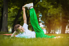 Happy kid is doing exercises in the park Stock Photos