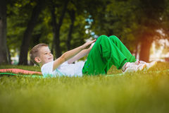 Happy kid is doing exercises in the park Stock Photography