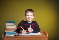 Happy kid doing homework with thumb up, books on table. royalty free stock photo