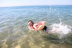 Happy smiling child swims in the sea. royalty free stock photos