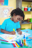 Happy kid drawing on his sheet Royalty Free Stock Photography