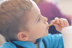 Happy kid with drinking straw looking up Stock Images