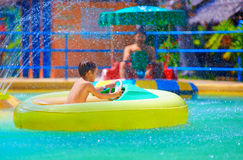 Happy kid driving toy water boat in aqua park Stock Photography