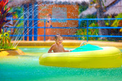 Happy kid driving toy water boat in aqua park Stock Image