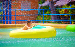 Happy kid driving toy water boat in aqua park Royalty Free Stock Images