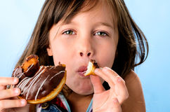 Happy kid eating a doughnut Stock Images