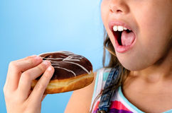 Happy kid eating a doughnut Stock Photos