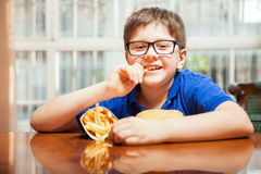 Happy kid eating french fries Royalty Free Stock Photos
