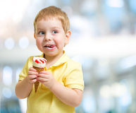 Happy kid eating icecream on blurred background Royalty Free Stock Photography