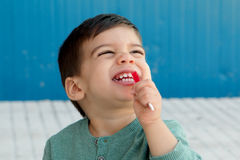 Happy kid eating a lollipop Stock Photography