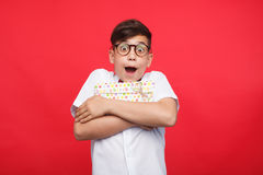 Happy kid embracing giftbox. Little boy in glasses looking happily at camera and embracing giftbox on red background stock photo