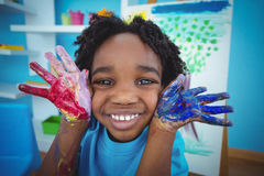 Happy kid enjoying arts and crafts painting. With his hands Royalty Free Stock Photo