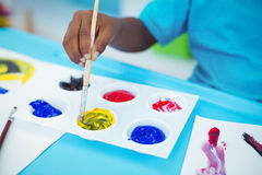 Happy kid enjoying arts and crafts painting. At their desk royalty free stock photos