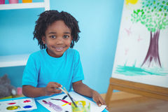 Happy kid enjoying arts and crafts painting. At their desk stock photography