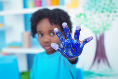 Happy kid enjoying painting with his hands stock photo