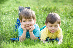 Happy kid enjoying sunny late summer and autumn day in nature on green grass. Happy two brothers kid enjoying sunny late summer and autumn day in nature on Stock Photo
