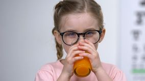 Happy kid in eyeglasses drinking carrot juice closeup, strong vision, vitamin A. Stock footage stock footage