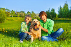 Happy kid, father and dog sit in park on grass. In summer Stock Image