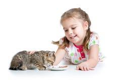 Happy kid feeding kitten Stock Photos
