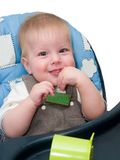 Happy kid at feeding table. Smiling baby sitting at feeding table and suck finger at home Royalty Free Stock Image