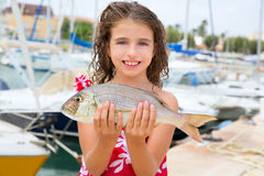 Happy kid fisherwoman with dentex fish catch Royalty Free Stock Images